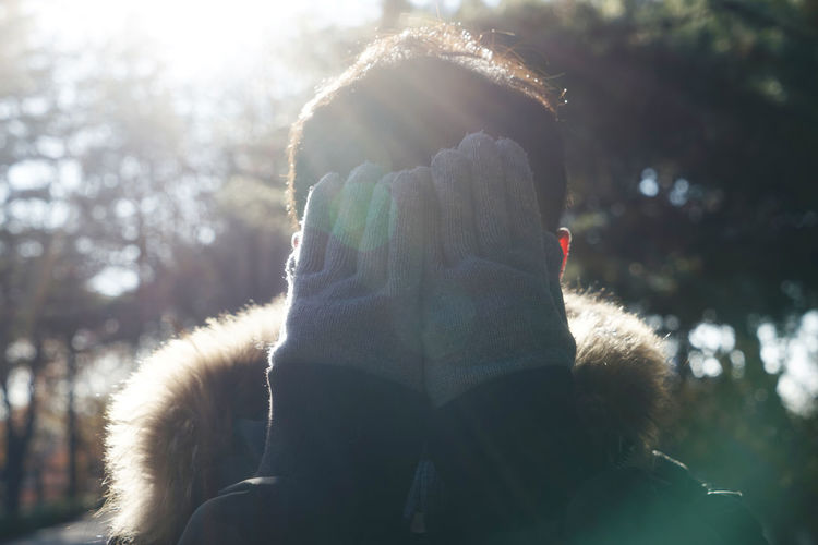 Close-Up Of Man Wearing Warm Clothing Covering Face With Hands During Sunny Day