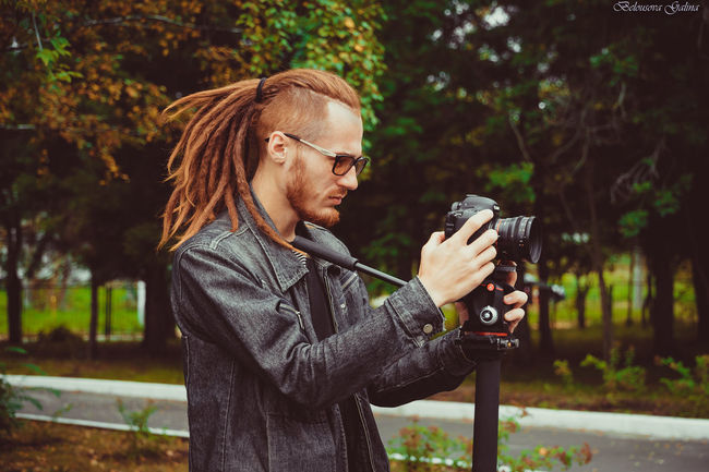 Camera - Photographic Equipment Day Digital Camera Digital Single-lens Reflex Camera Eyeglasses  Focus On Foreground Holding Leisure Activity Lifestyles Nature One Person Outdoors People Photographer Photographing Photography Themes Real People Side View Technology Tree Young Adult Young Women