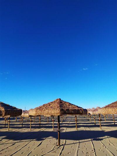 Built structure on desert against clear blue sky