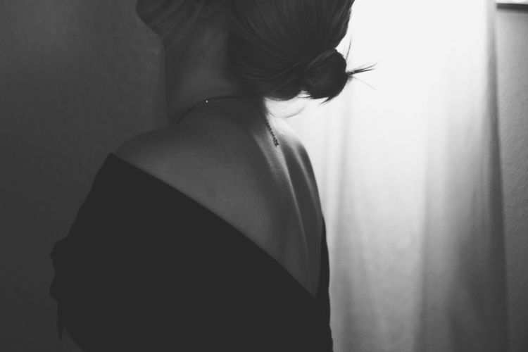 Side view of woman wearing backless dress at home