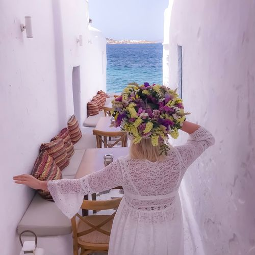 Rear View Of Woman Wearing Flowers While Walking In Alley Against Sea