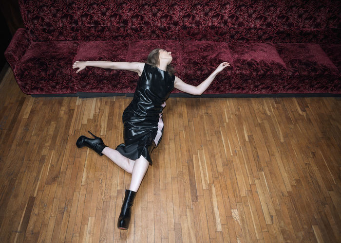 High angle view of woman posing on hardwood floor at home