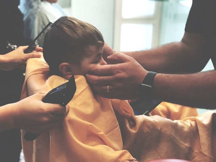 Cropped Hands Of People Cutting By Hair In Saloon