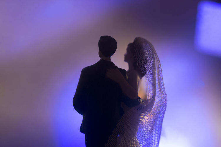 Rear view of couple kissing against illuminated light