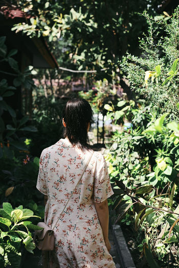 Adult Casual Clothing Day Floral Pattern Focus On Foreground Green Color Growth Hairstyle Leisure Activity Lifestyles Nature One Person Outdoors Plant Real People Rear View Standing Three Quarter Length Tree Women