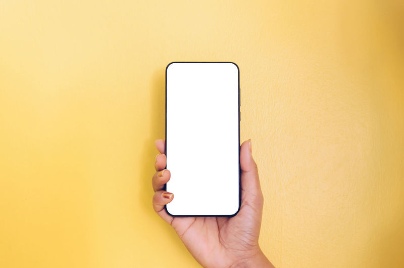 Close-up of hand holding smart phone against yellow wall