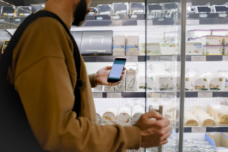 Midsection of man using mobile phone in store