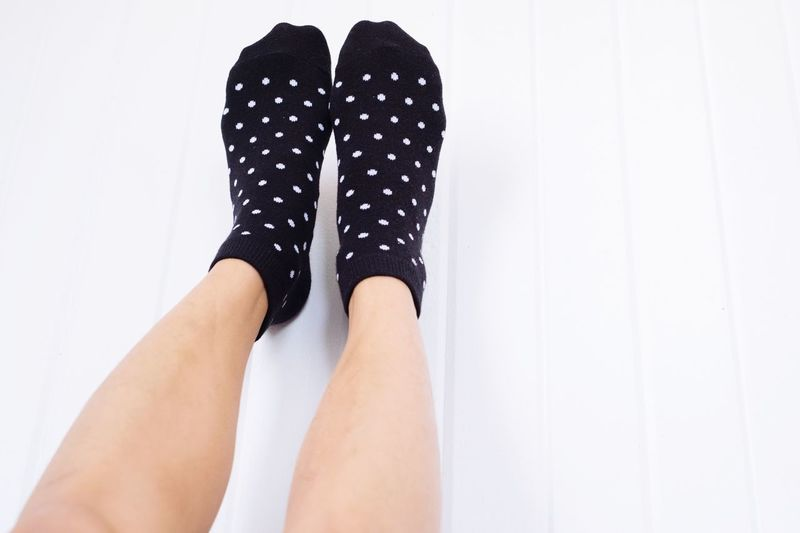 A pair of feet with polka dot socks leaning on the wall. Blackandwhite Polka Dot Winter Laid Back Lazy Day Casual Home Sweet Home Cozy At Home Warm Wearing Socks Chill Relaxation Relaxing Time Upside Down EyeEm Selects Low Section Human Leg Human Body Part Body Part Real People One Person Human Foot Women Lifestyles White Background Limb Personal Perspective Leisure Activity Fashion Indoors