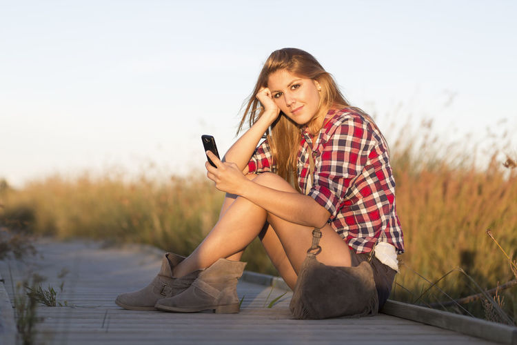 Young beautiful woman looking at the camera while holding the smartphone in her hand Answering Communication Connection Day Full Length Happiness Holding Leisure Activity Long Hair Mobile Phone One Person Outdoors Photo Messaging Portable Information Device Portrait Sitting Smart Phone Smiling Technology Teenage Girls Teenager Telephone Text Messaging Using Phone Wireless Technology