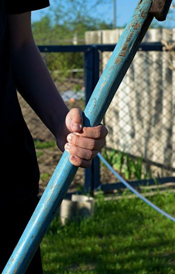 Cropped image of man holding hands on railing