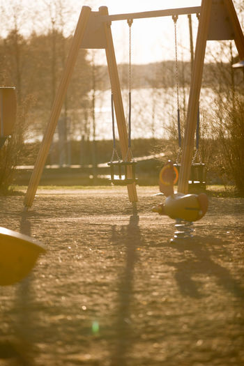 Playground Swing Childhood Day Nature Sunlight Selective Focus Water Outdoor Play Equipment Leisure Activity Absence Park Outdoors Playing Park - Man Made Space Lake Fun Reflection