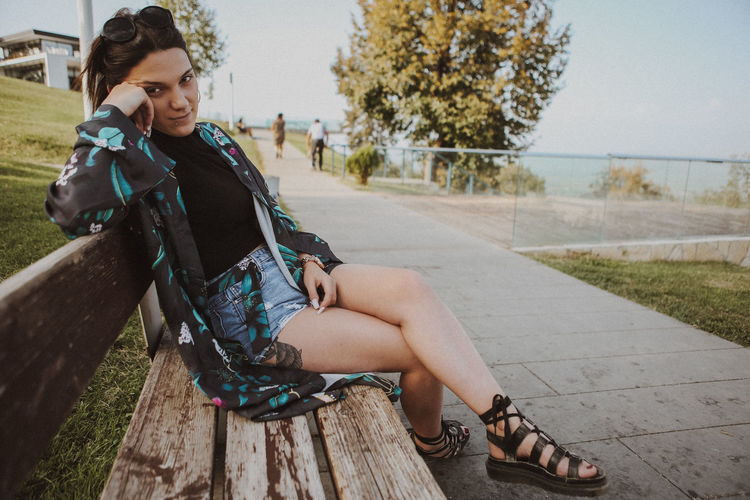 Full Length Portrait Of Young Woman Sitting By Footpath On Bench