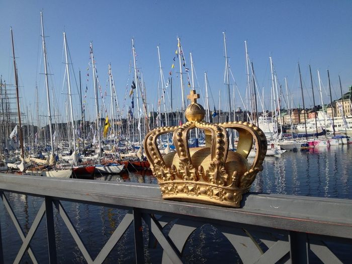 Close-up of crown on railing at harbor against sky