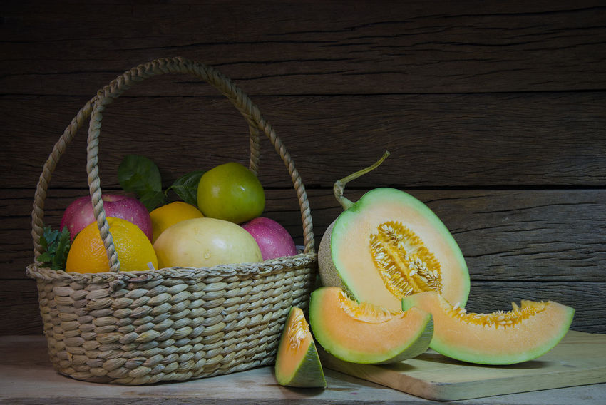 Fresh cantaloupe melons sliced on the Chopping board and the basket of fruit have an apple and orange on wooden table. Still life image. Agriculture Apple Cut Melons Orange Wicker Basket Cantaloupe Close-up Day Food Food And Drink Freshness Fruit Healthy Eating Indoors  Juicy No People SLICE Table