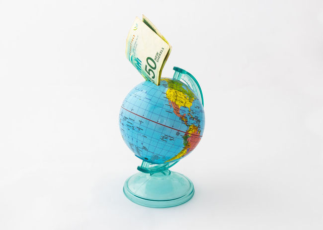 A money box made in the shape of a planet Earth globe with an inserted banknote worth fifty Israeli shekels in the money slot at the top isolated on a white background. Business Currency Earning Earth Isolated Art Bank Banknote Buy Cash Coin Coins Design Exchange Finance Globe Israel Money Pay Planet Shekel Stock Studio Shot Wealth White Background