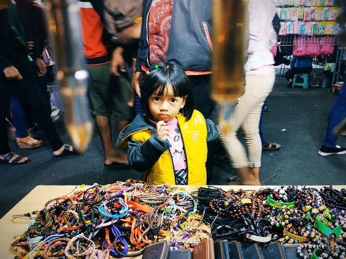 Portrait Of Cute Girl Standing By Bracelet Stall At Street Market