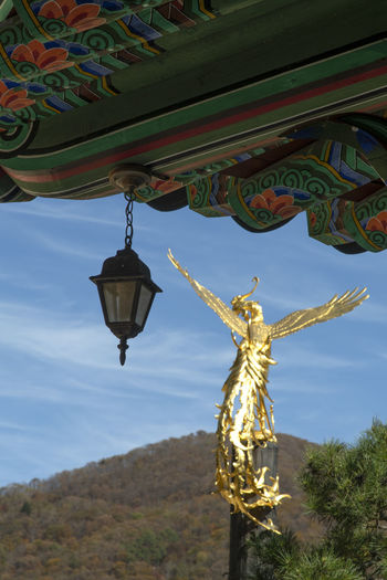 Low angle view of angel sculpture hanging at temple