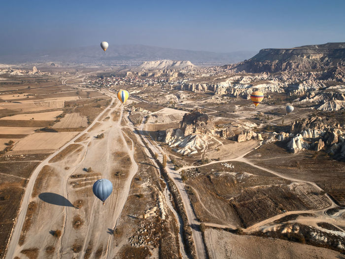 Aerial view of hot air balloon over landscape against sky