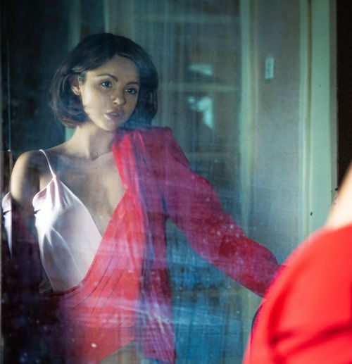 Portrait of woman with reflection on window