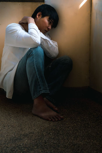 Side view of man sitting on floor
