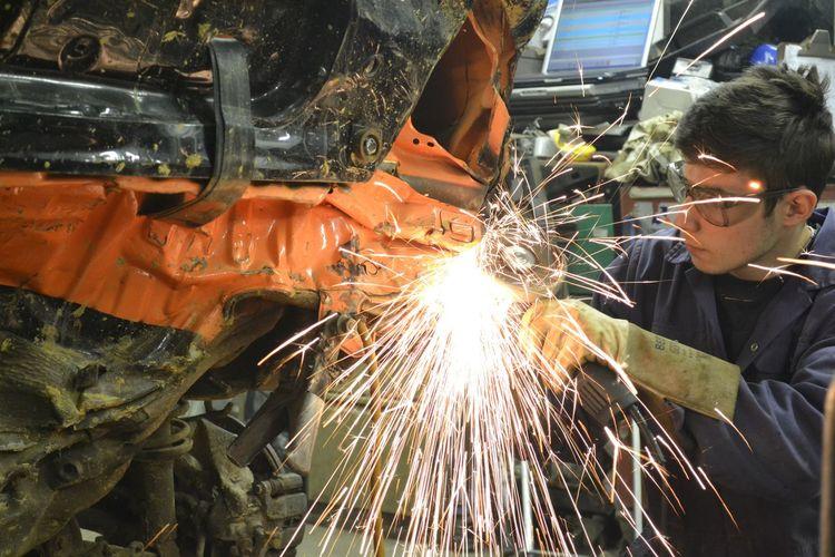Man welding car in garage