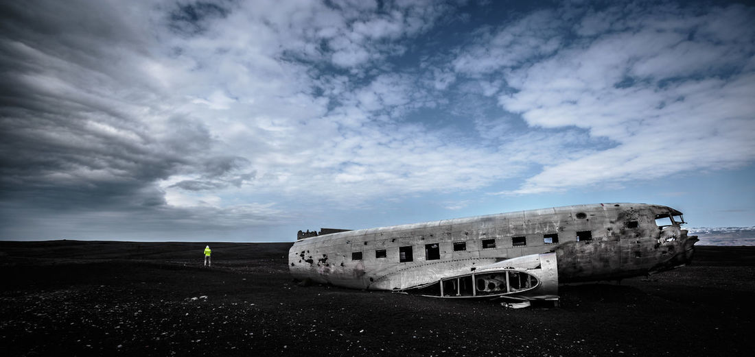 Person By Airplane Wreckage On Field Against Cloudy Sky