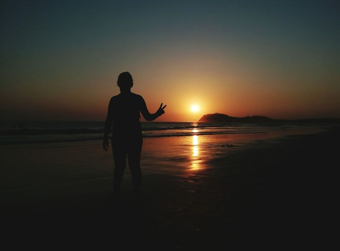 Silhouette person gesturing peace sign while standing at beach during sunset