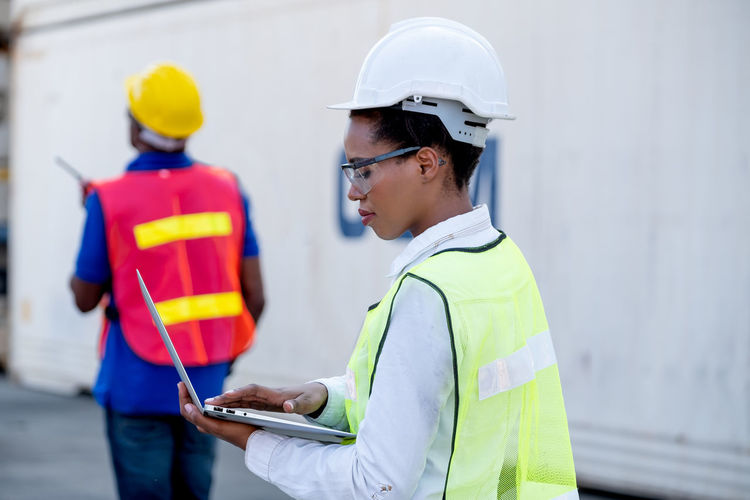 Rear view of man working with mobile phone