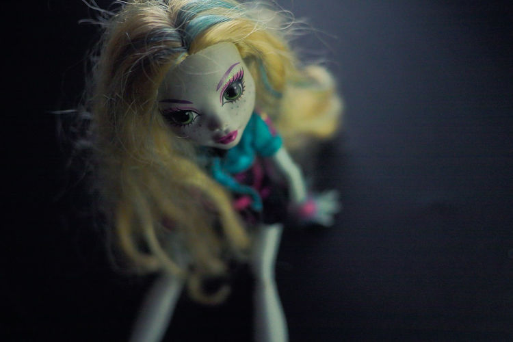 Close-up of doll on black background