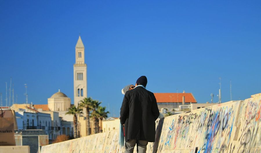 Rear view of people looking at city buildings against blue sky