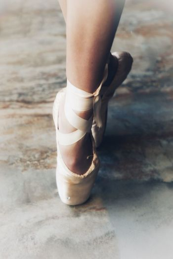 Low section of ballet dancer tiptoeing on tiled floor