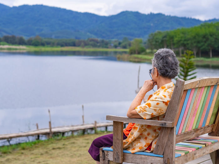 Side view of a elderly woman sitting on chair side the lake