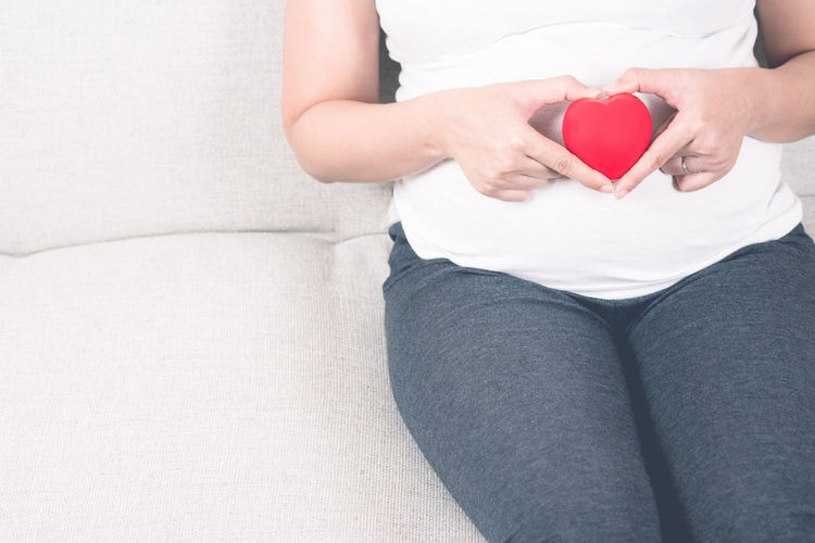 Midsection of pregnant young woman holding heart shape on sofa at home