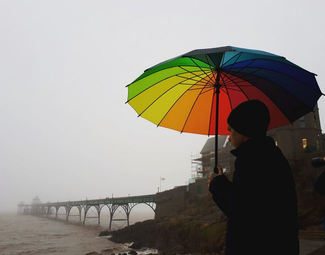 Teenage Boy Holding Umbrella While Standing Against Sea During Foggy Weather