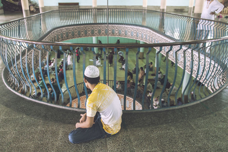 High Angle View Of Man Looking At People Praying In Mosque