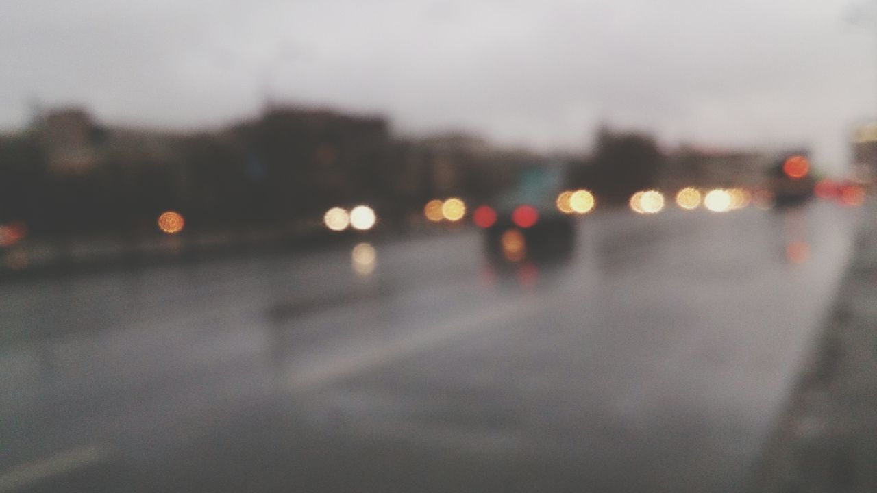 Defocused Lights On Road During Foggy Weather At Dusk