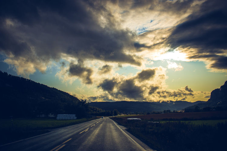 View of road along landscape against cloudy sky