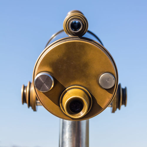 Low angle view of coin-operated binoculars against sky
