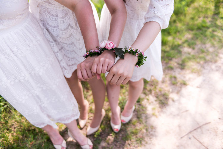 Low section of bridesmaid with flower bracelets