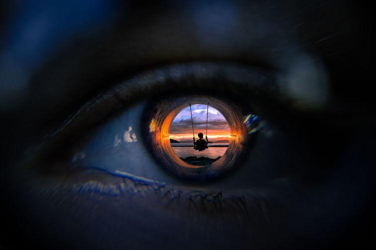 Digitally generated image of boy swinging at beach reflecting on man eyeball