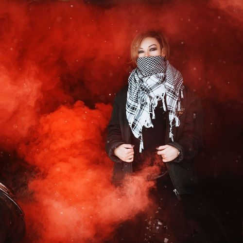 Portrait of young woman wearing scarf while standing amidst red smoke