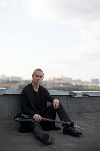 Full length portrait of young man with guitar sitting on building terrace