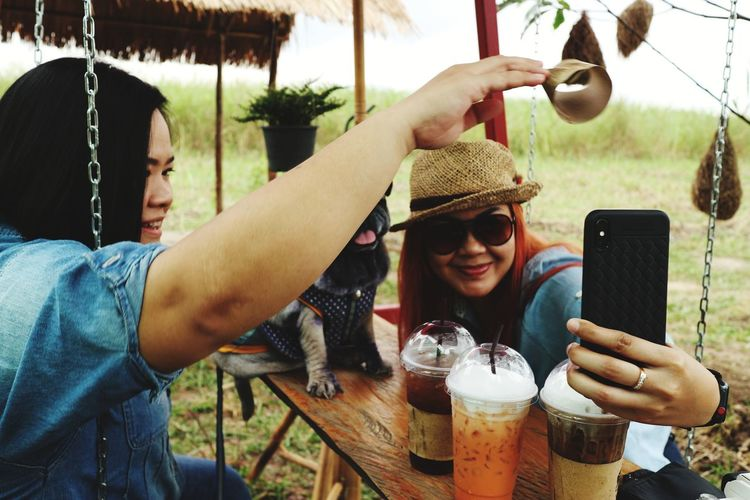 Women taking elfie while sitting with dog outdoors