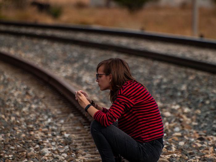 Girl sitting on railroad track