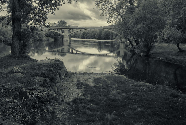 Reflection of arch bridge in river amidst trees against cloudy sky