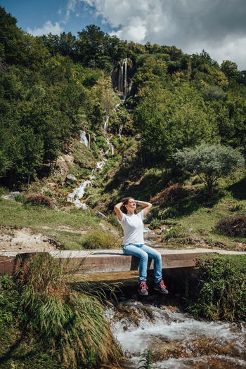 Young girl sitting on a bridge with a big waterfall in the background Plant Tree Full Length Real People One Person Nature Growth Leisure Activity Casual Clothing Lifestyles Day Women Beauty In Nature Green Color Adult Water Non-urban Scene Sitting Mid Adult Outdoors Young Adult Young Women Waterfall Hiking Adventure This Is Natural Beauty