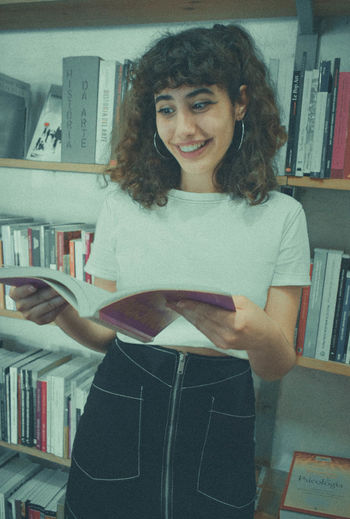 Publication Book Shelf One Person Looking At Camera Indoors  Portrait Bookshelf Casual Clothing Front View Women Real People Home Interior Smiling Young Adult Hairstyle Education Young Women Lifestyles
