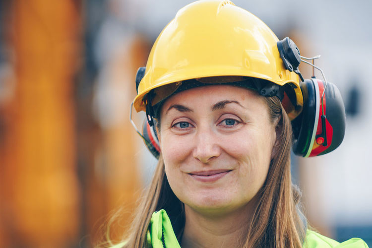 Portrait of smiling female worker wearing hardhat and ear muffs