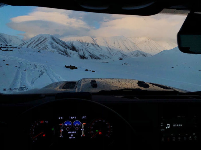 Aerial view of mountain seen through car windshield during winter