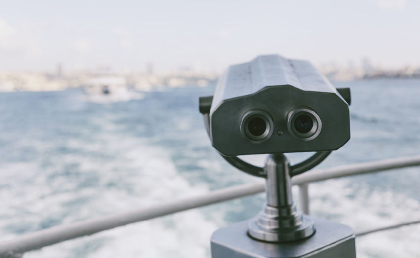Coin-Operated Binocular On Boat Sailing In Sea Against Sky
